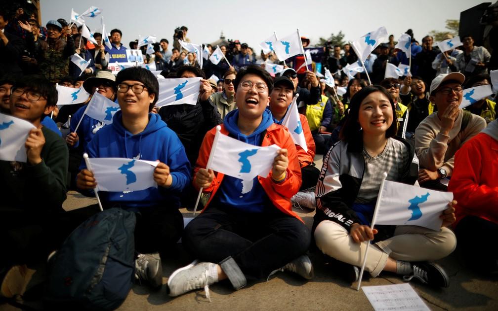 Sul-coreanos segurando bandeiras da unificação coreana assistem noticiário sobre a cúpula entre as duas Coreias e comemoram, perto da Zona Desmilitarizada, em Paju, na sexta-feira (27) (Foto: Reuters/Kim Hong-ji)