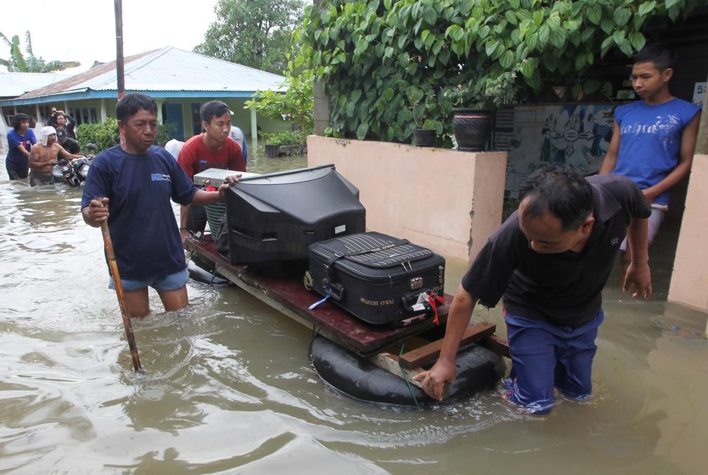 Moradores carregam seus pertences com uma jangada depois da enchente em Bengkulu, na Indonésia, neste sábado (27). — Foto: Antara Foto/David Muharmansyah/ via Reuters