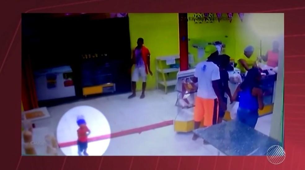 Criança 'passeia' por dentro da loja enquanto bandidos saqueiam clientes e o caixa da padaria (Foto: Reprodução/TV Subaé)