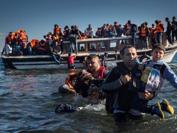 Refugiados da Síria e do Iraque desembarcam na ilha grega de Lesbos após chegar em um barco de madeira a partir da costa turca. O governo da Grécia diz preaprar um programa de assistência para lidar com o crescente número de refugiados que chegam ao país (Foto: Santi Palacios/AP)