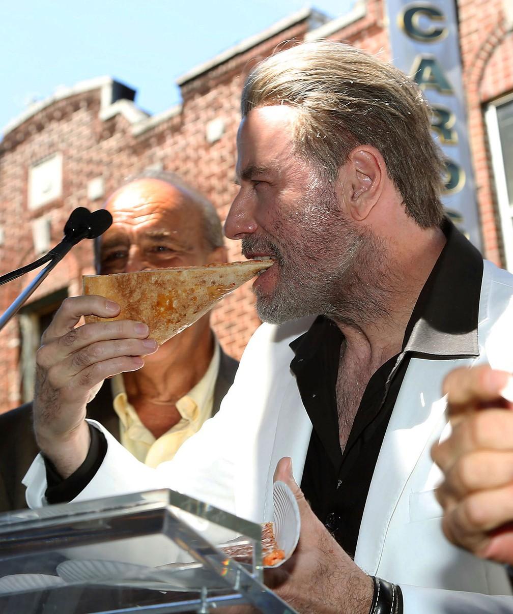 -  Imagem divulgada pela Starpix mostra o ator John Travolta, comendo um pedaço de pizza da Lenny  39;s, no Brooklyn, nesta terça-feira  12 ; local serv