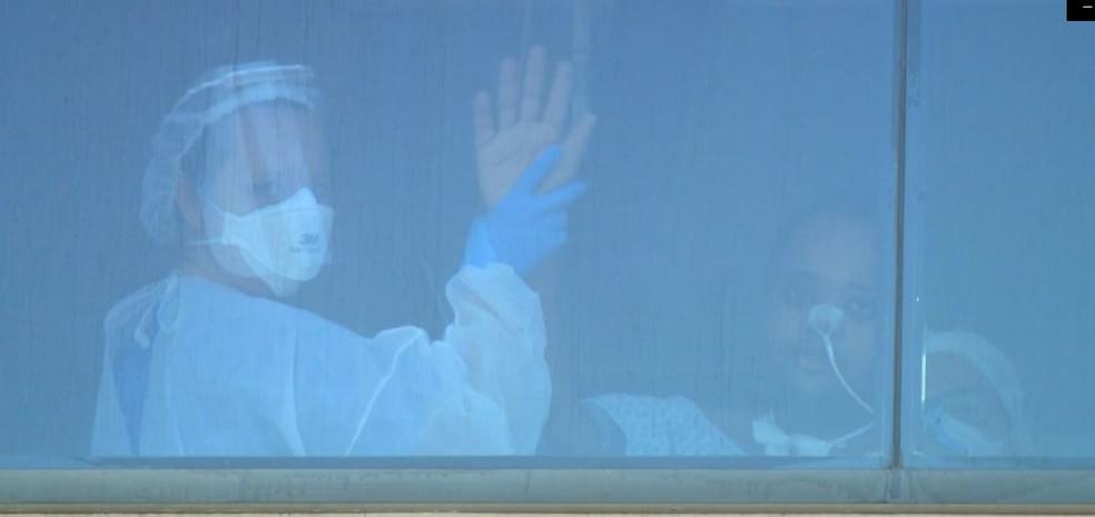 Da janela, Daniel Justino acena para o pai, que vai diariamente para frente de hospital em Indaiatuba rezar por ele — Foto: Ricardo Custódio/EPTV
