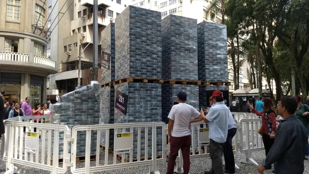 Na ação, cédulas falsas de dinheiro foram organizadas em uma estrutura montada na Rua XV de Novembro (Foto: João Salgado/RPC)