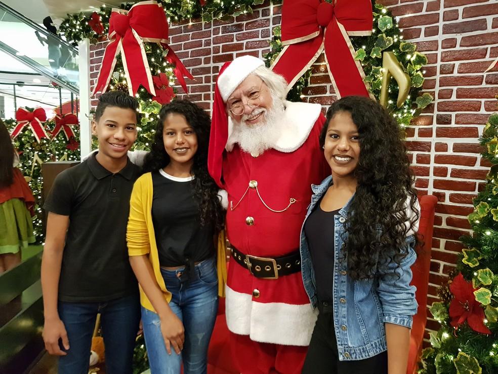 3b1d4a71d ... Trigêmeos de 15 anos aproveitam oportunidade e tiram foto gratuita com Papai  Noel em Shopping de