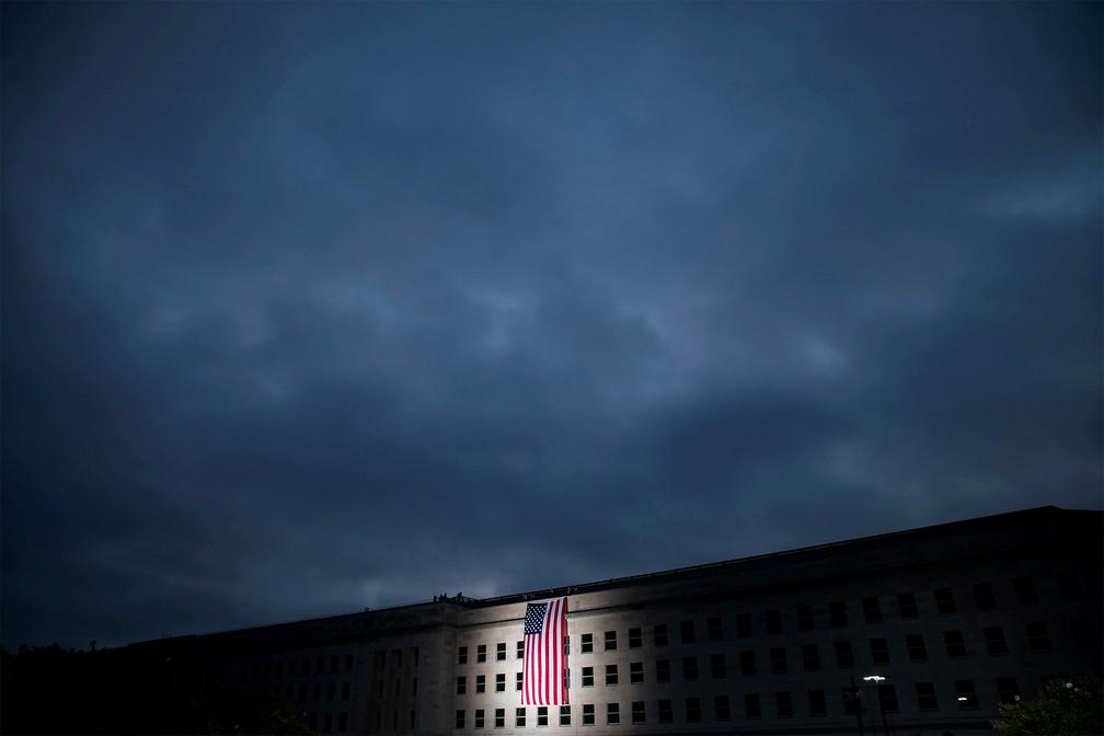 Bandeira dos EUA é vista na fachada do Pentágono em Arlington, Virgínia, em cerimônia durante o amanhecer marcando os 18 anos dos atentados de 11 de Setembro — Foto: Al Drago/Reuters