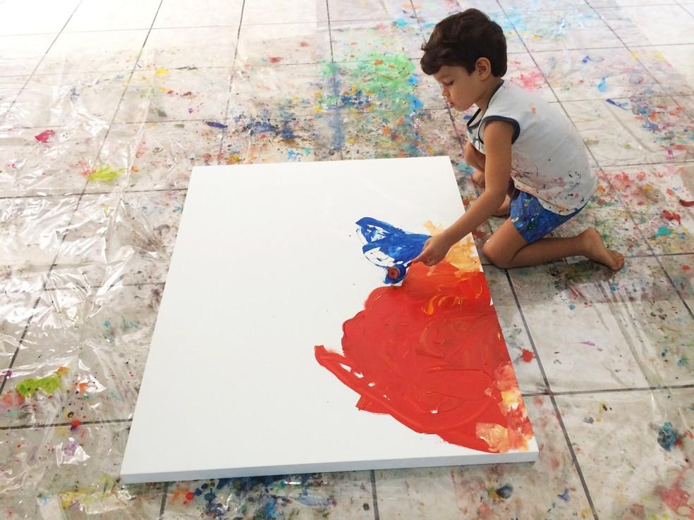 Os pais de Mateus Rosa organizam um cantinho em casa para que o menino pinte as telas, em Campina Grande — Foto: Érica Ribeiro/G1