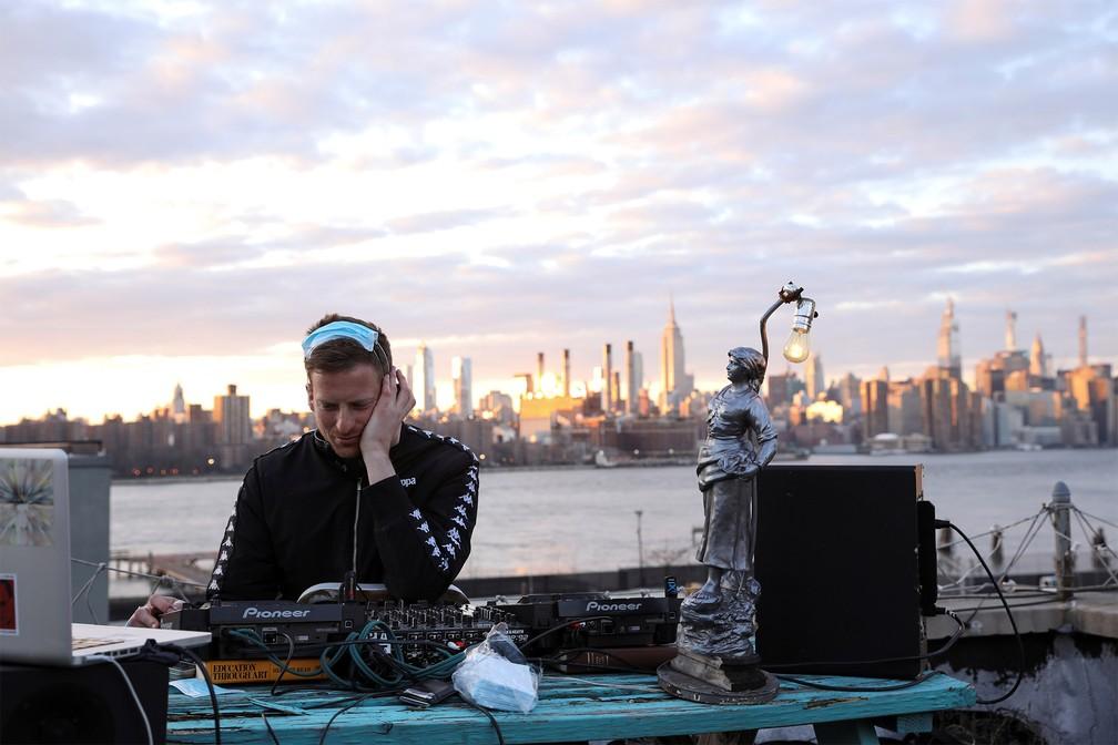 21 de março - O DJ e produtor de eventos Nash Petrovic faz uma apresentação do telhado de seu apartamento no Brooklyn, em Nova York, transmitida ao vivo por stream durante quarentena devido à pandemia de coronavírus — Foto: Caitlin Ochs/Reuters