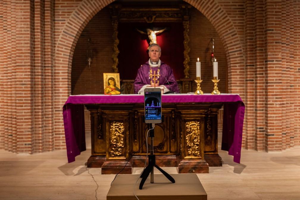 15 de março - O padre católico Jesus Higueras, da paróquia de Santa Maria de Cana, é visto em um smartphone durante uma missa transmitida por vídeo ao vivo em Pozuelo de Alarcon, nos arredores de Madri, na Espanha — Foto: Bernat Armangue/AP