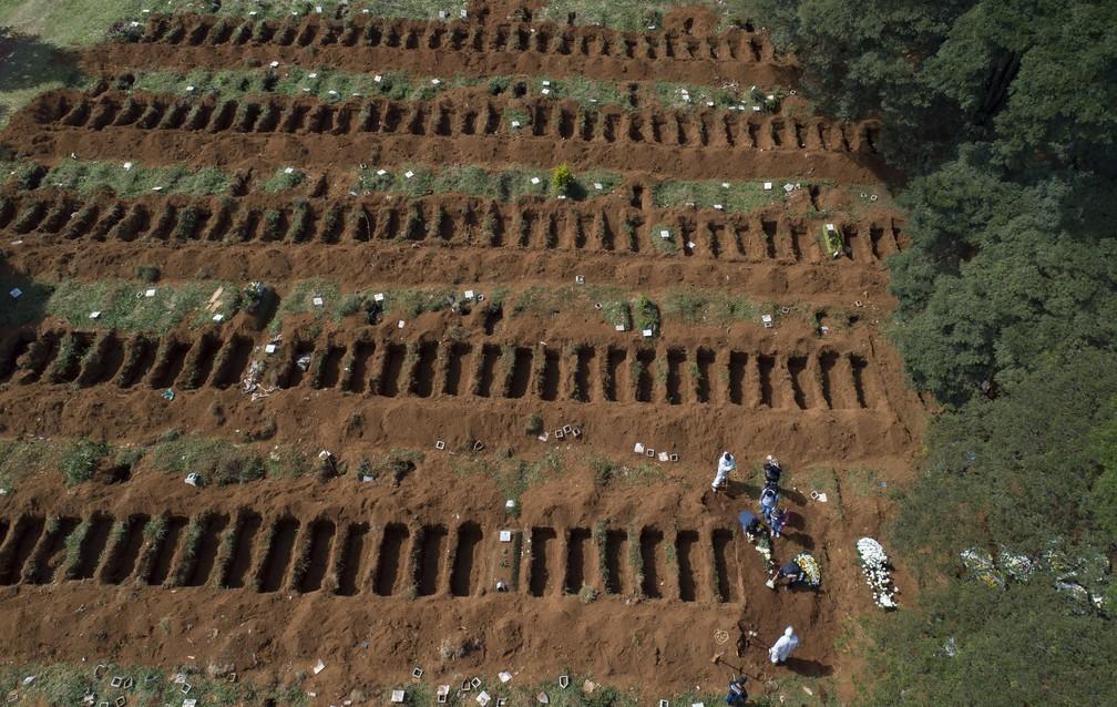 1º de abril - Funcionários enterram uma pessoa no cemitério de Vila Formosa, em São Paulo — Foto: Andre Penner/AP