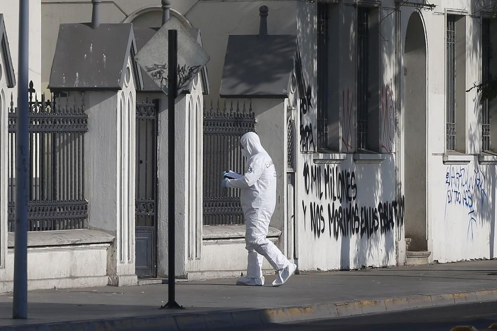 Policiais examinam cena de ataque no Chile. Pelo menos três igrejas em Santiago foram danificadas a poucos dias da visita do papa ao país (Foto: Pablo Vera/AFP)