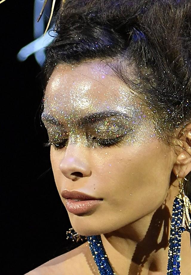 O glitter, que apareceu com destaque absoluto nas belezas do ano, ganha ares de Halloween em versão exagerada, aplicado até na raiz dos cabelos, como na passarela de inverno 2018 alta-costura de Guo Pei (Foto: Imaxtree)