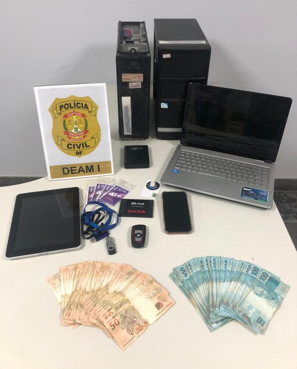 Na casa do suspeito de sugar daddy, policiais da Deam-DF apreenderam dinheiro, celular e computadores — Foto: Polícia Civil do DF /reprodução