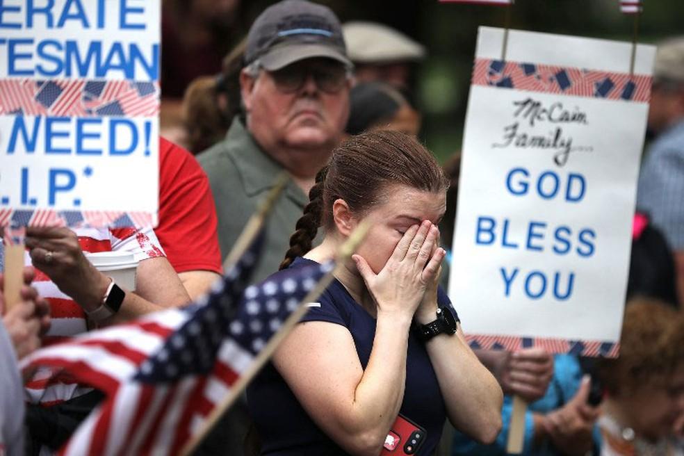 Mulher chora durante a passagem de comitiva com corpo do senador John McCain pelo Memorial dos Veteranos do Vietnã, neste sábado (1º)  (Foto: Chip Somodevilla / Getty Images / AFP)