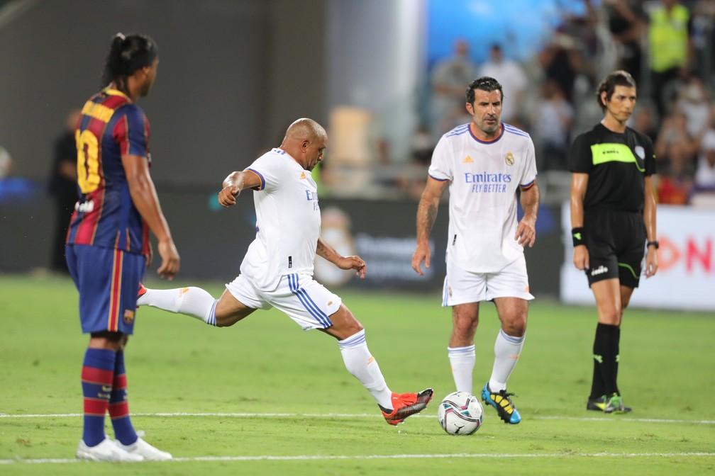 Roberto Carlos cobra falta observado de perto por Ronaldinho Gaúcho e Luis Figo, em amistoso de lendas do Barcelona e do Real Madrid — Foto: Abir Sultan/EFE