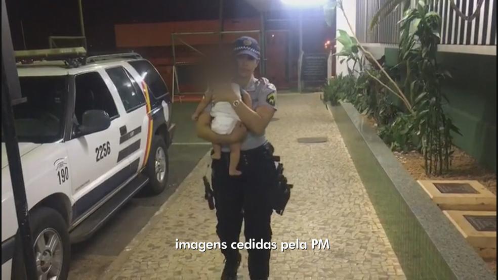 Cabo da PM levando bebê a delegacia (Foto: Reprodução)