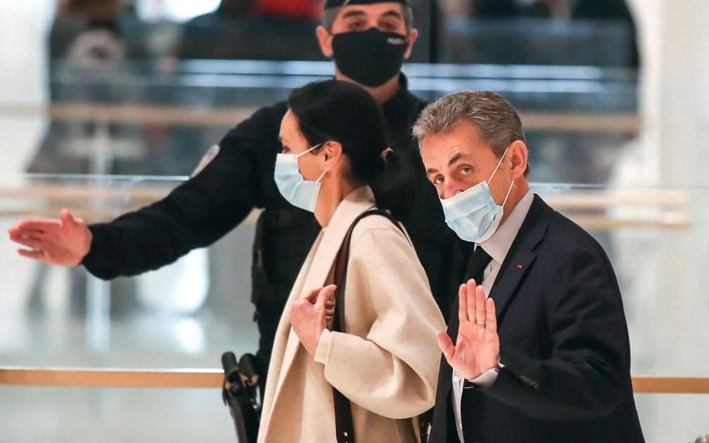 Ao lado de sua advogada, o ex-presidente francês Nicolas Sarkozy acena ao chegar à corte em Paris — Foto: AP Photo/Michel Euler