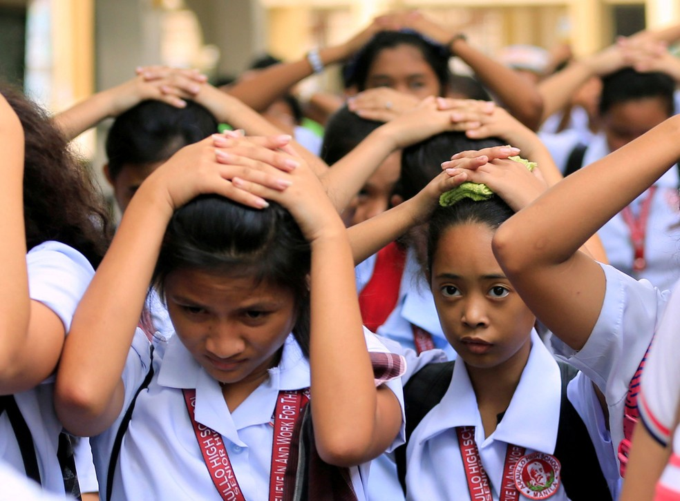 Estudantes protegem a cabeça ao deixar escola, em Manila, após terremoto atingir o norte das Filipinas nesta sexta-feira (11)  (Foto: Romeo Ranoco/ Reuters)