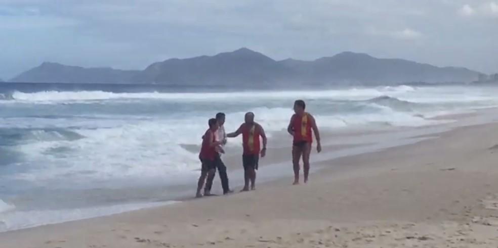 Vítima de queda do helicóptero chega à praia (Foto: Reprodução/Redes sociais)