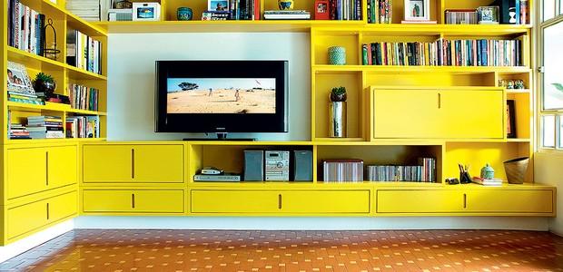 A arquiteta Cláudia Pecego projetou uma estante de MDF com acabamento em gofrato amarelo. Para amenizar o visual marcante, a profissional solicitou que a base da estante fosse pintada de branco, dando a impressão de que o móvel está suspenso (Foto: Célia Weiss/Casa e Jardim)