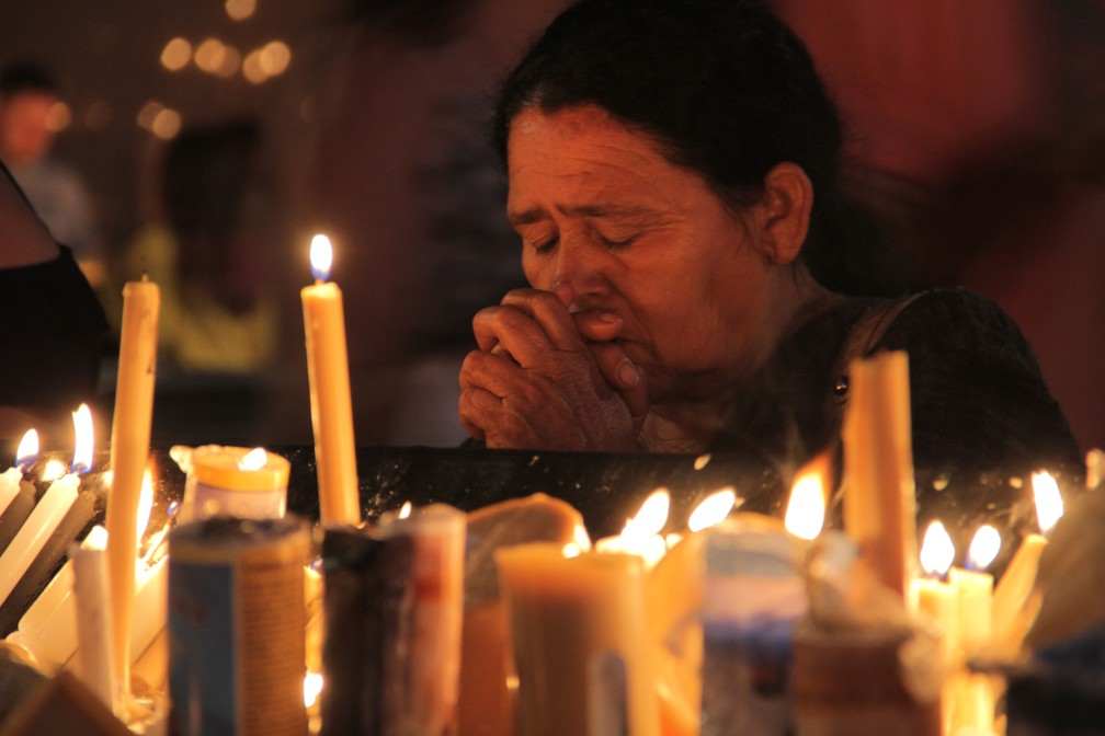 Com a vela acesa, fiéis fazem orações destinadas à Padroeira (Foto: Carlos Santos/G1)