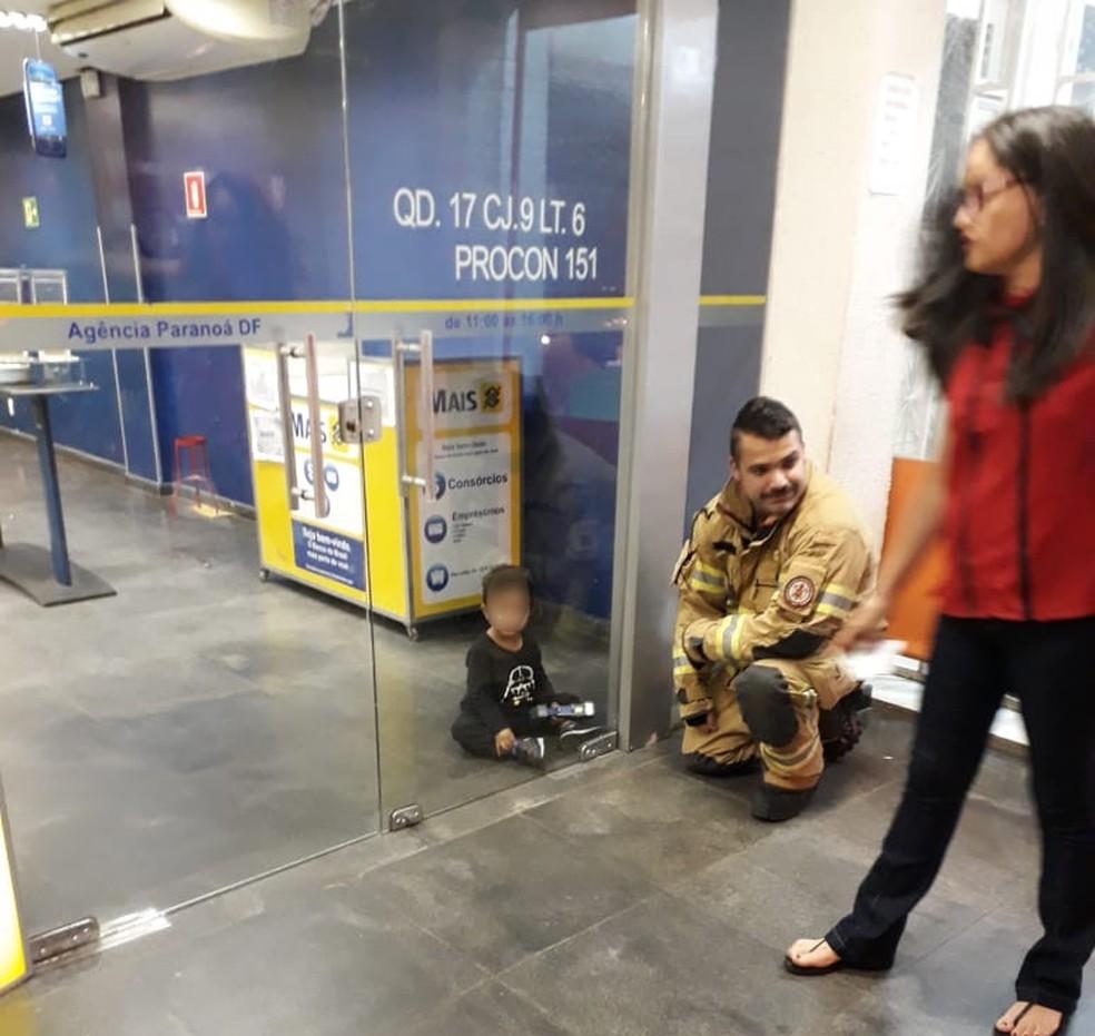Criança sendo resgatada na agência bancária na noite da última terça (12) (Foto: PMDF/Divulgação)
