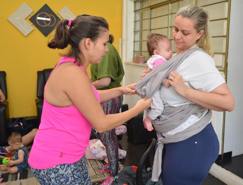 Carolliny auxilia as alunas na colocação do sling antes da atividade em São Carlos (Foto: Ana Marin/EPTV)