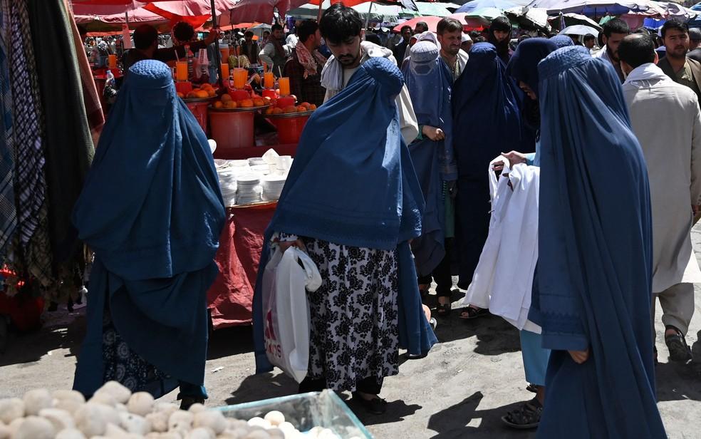 Mulheres afegãs usam burca ao fazer compras em feira em Cabul, no dia 28 de agosto — Foto: Aamir Qureshi/AFP