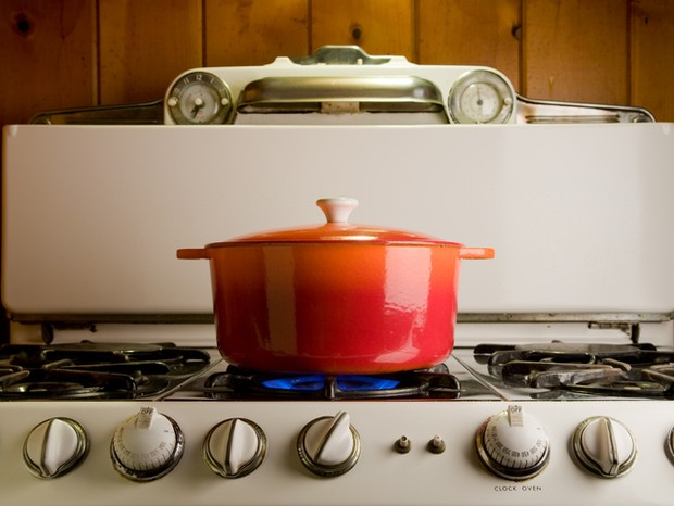 red cast iron pot cooking on antique stove (Foto: Getty Images)