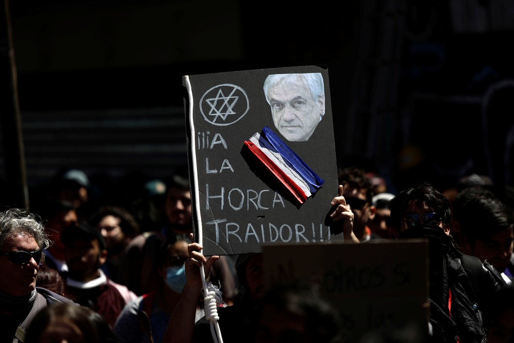 Manifestantes exibem cartaz com rosto do presidente do Chile, Sebastian Piñera: 'À forca, traidor' — Foto: Juan Gonzalez/Reuters