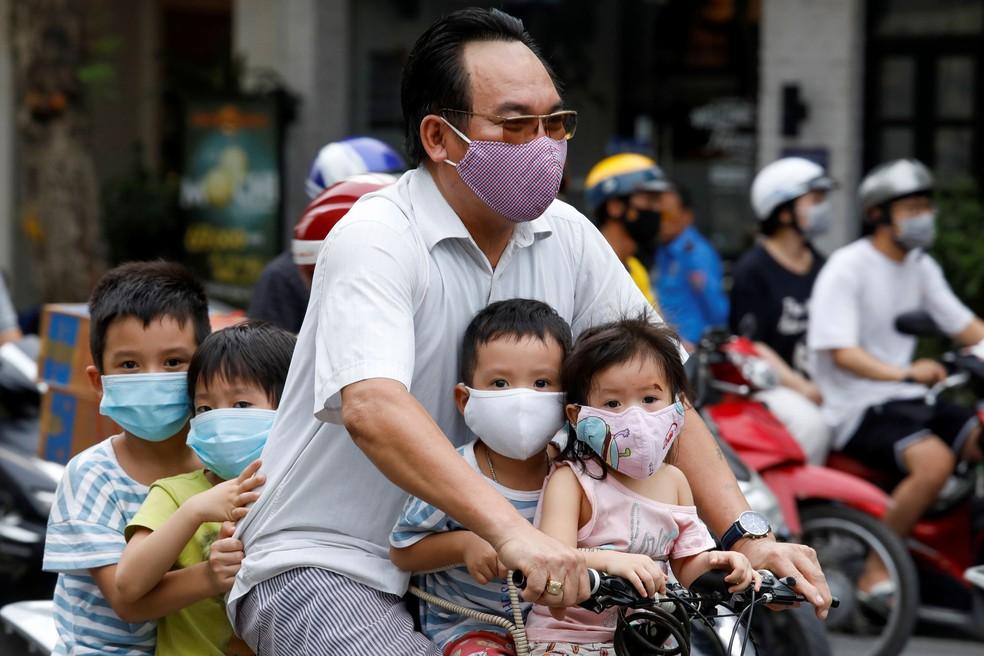 Homem e seus filhos, todos usando máscaras, andam de bicicleta em rua de Hanói,  no Vietnã, nesta segunda-feira (27)  — Foto: Kham/ Reuters