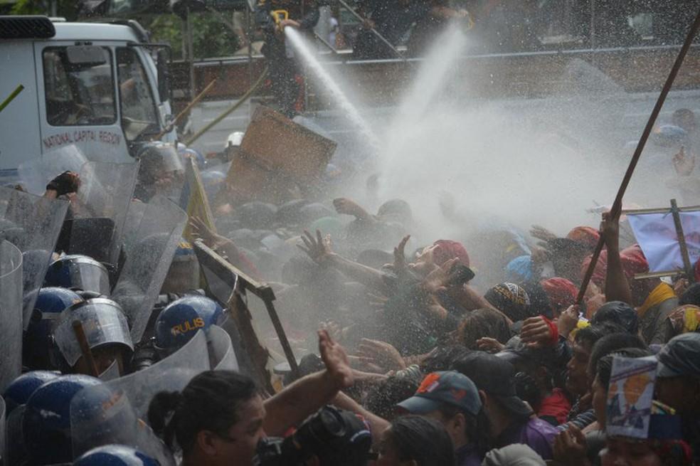 Polícia usa jatos de água para dispersar manifestantes que protestavam contra a presença do presidente americano, Donald Trump, na reunião de cúpula da Associação de Nações do Sudeste Asiático (ASEAN)   (Foto: Ted Aljibe / AFP)