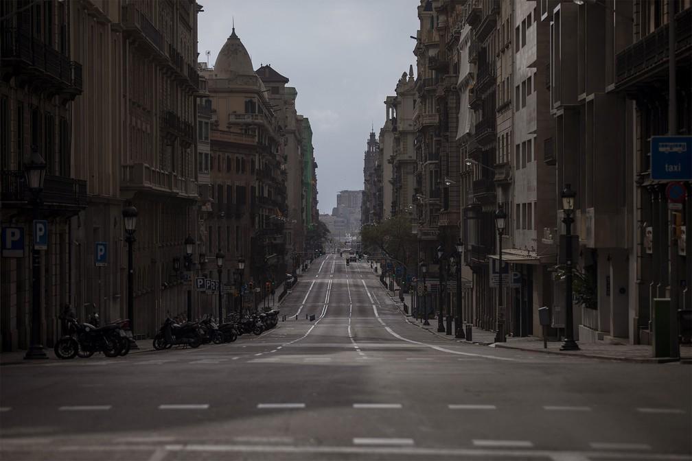 BARCELONA (Espanha) - A Via Laietana é vista vazia em Barcelona, após autoridades passarem a controlar o movimento em lugares públicos da cidade, no domingo (22) — Foto: Emilio Morenatti/AP