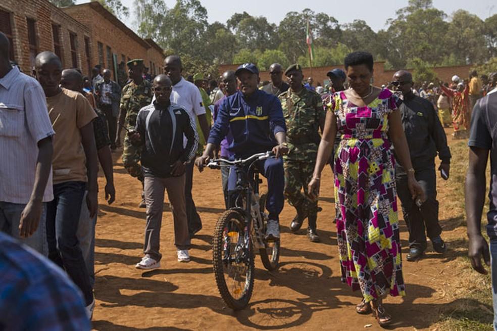 O presidente do Burundi, Pierre Nkurunziza, chega de bicicleta para votar em eleições presidenciais (Foto: Phil Moore/AP)