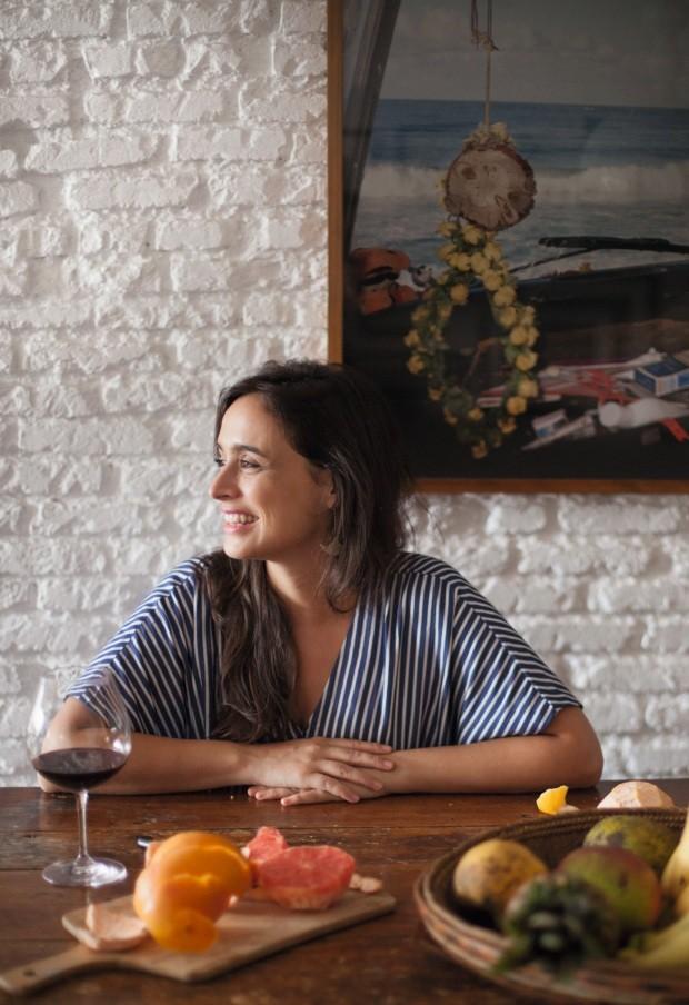 Da mesa antiga de madeira, Bel observa a quaresmeira florida através da janela. Ao fundo, a fotografia de Christian Gaul, da Compota Edições Limitadas, foi presente de uma amiga (Foto: Mayra Azzi / Editora Globo)