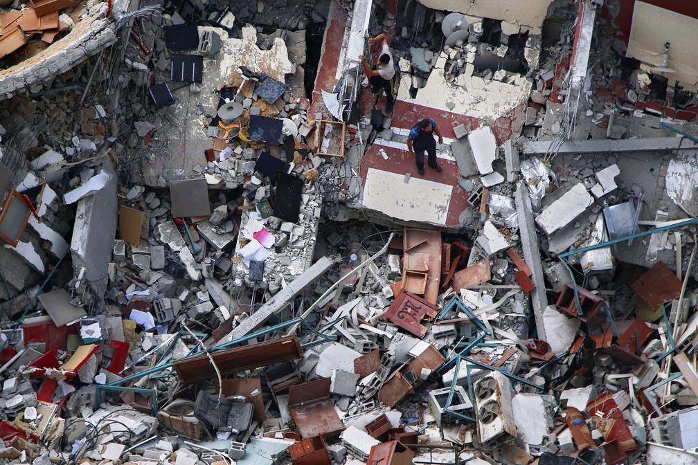 Palestinos inspecionam o prédio destruído que abriga os escritórios da Associated Press e outros meios de comunicação, após ter sido atingido na semana passada por um ataque aéreo israelense, na Cidade de Gaza — Foto: Hatem Moussa/AP