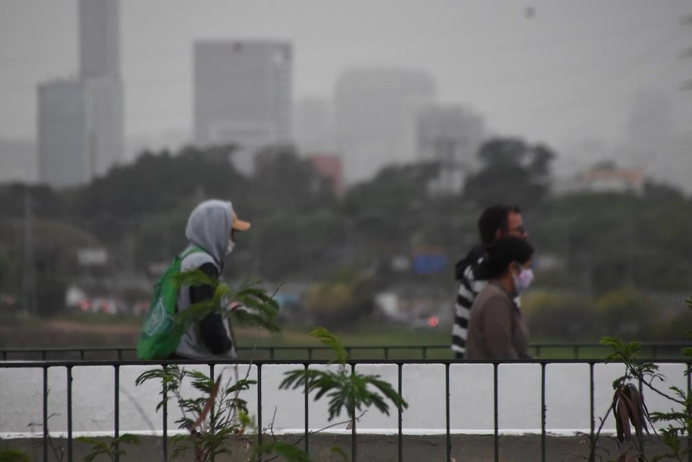 Pedestres se protegem do frio e da garoa no dia 22 de setembro de 2021 na Ponte do Jaguaré, em São Paulo (SP) — Foto: RONALDO SILVA/FUTURA PRESS/ESTADÃO CONTEÚDO
