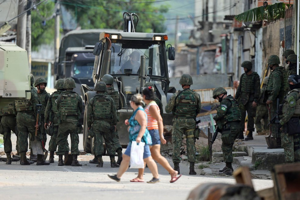 Mulheres atravessam uma rua observando a ação de militares na remoção de bloqueios erguidos por traficantes na Vila Kennedy, na Zona Oeste do Rio de Janeiro (Foto: Wilton Junior/Estadão Conteúdo)