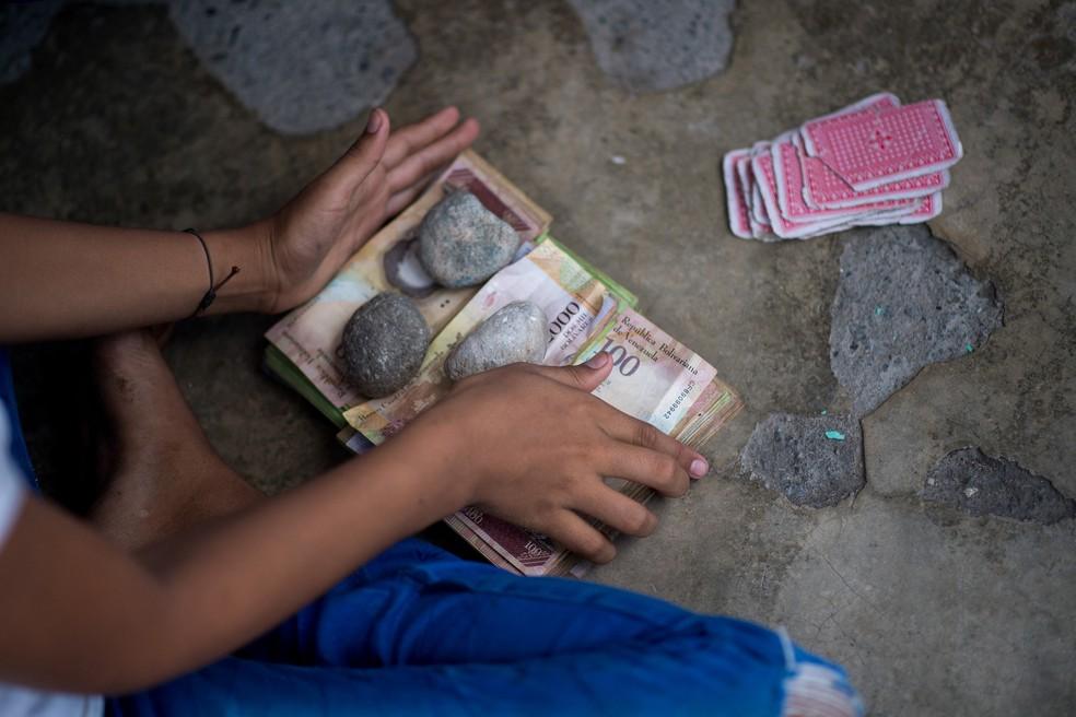 Crianças jogam cartas e apostam com notas de bolívar venezuelano não utilizadas em Puerto Concha, na Venezuela — Foto: Federico Parra/AFP