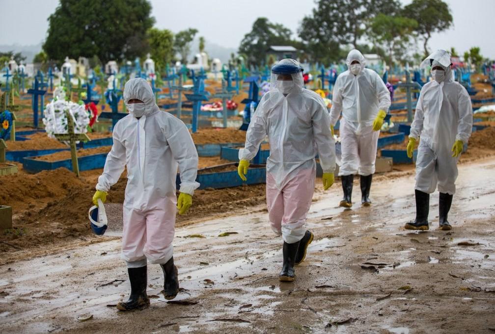 Pessoas usando roupas e equipamentos de proteção contra o coronavírus Sars-CoV-2 andam em meio a túmulos de vítimas da Covid-19 no cemitério Nossa Senhora Aparecida, em Manaus, no dia 25 de fevereiro. — Foto: Michael Dantas/AFP