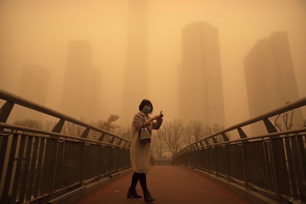 Mulher caminha sobre ponte de pedestres em meio a tempestade de areia no distrito comercial de Pequim — Foto: Mark Schiefelbein/AP