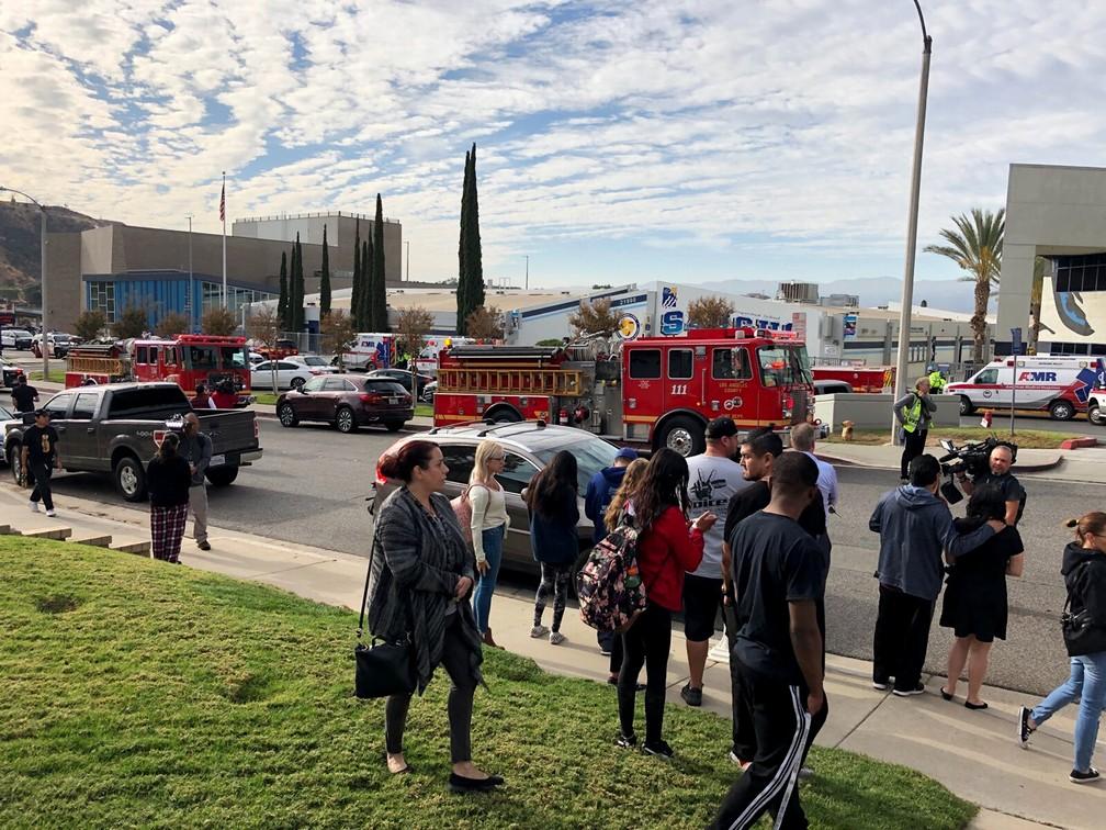 Pessoas aguardam alunos e informações do lado de fora da escola de ensino médio de Saugus, na Califórnia, depois de um tiroteio nesta quinta-feira (14). — Foto: Marcio Jose Sanchez/AP