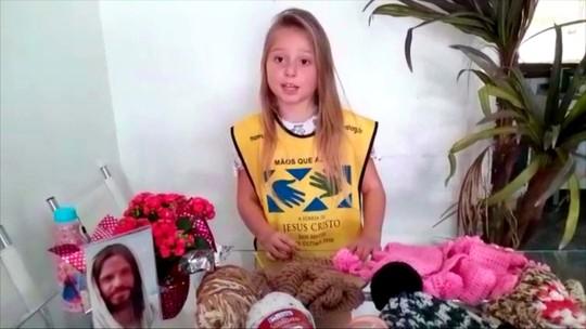 Menina de 8 anos faz cachecóis para doação
