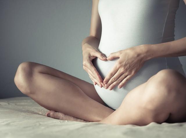 Mulher grávida com as mãos na barriga (Foto: Thinkstock)