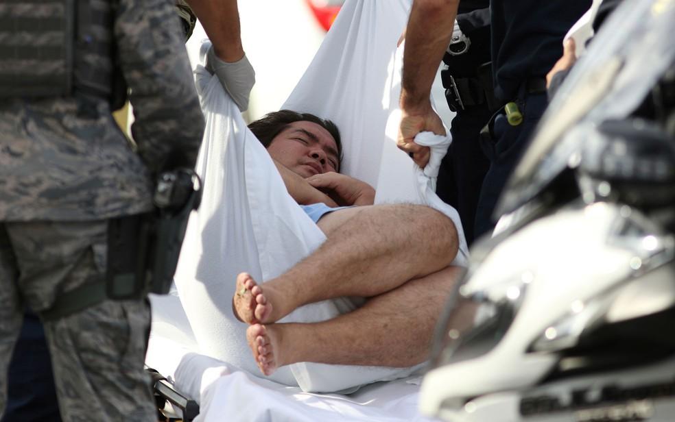 Um homem é levado por policiais da base Pearl Harbor — Foto: Caleb Jones / AP Photo
