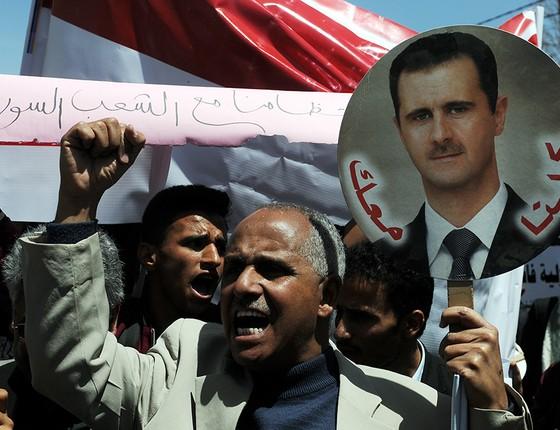 Manifestante pró-governo com foto do presidente sírio Bashar al-Assad, durante protesto contra ataques dos Estados Unidos em represália ao suposto uso de armas químicas (Foto: MOHAMMED HAMOUD/GETTYIMAGES)