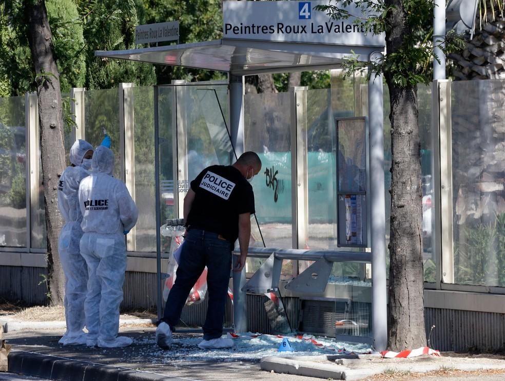 Policiais inspecionam ponto de ônibus atingido por carro nesta segunda-feira (21) em Marselha, na França  (Foto: Claude Paris/ AP)