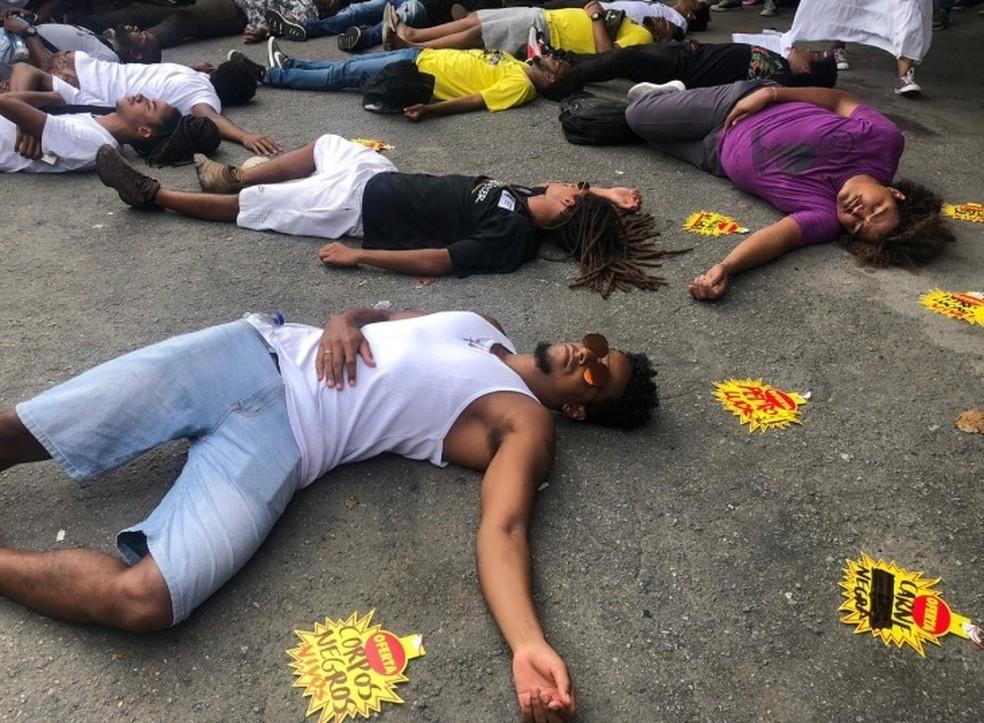 Homens se deitam no chão durante protesto — Foto: Matheus Rodrigues/G1