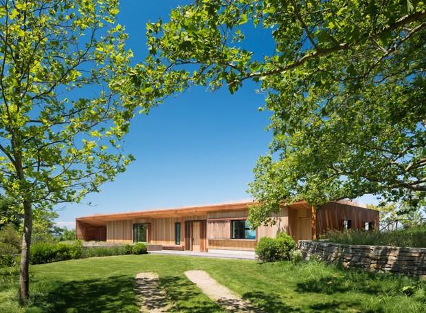 Os arquitetos usaram madeira para mesclar a casa com a paisagem (Foto: Michael Moran/ Reprodução)
