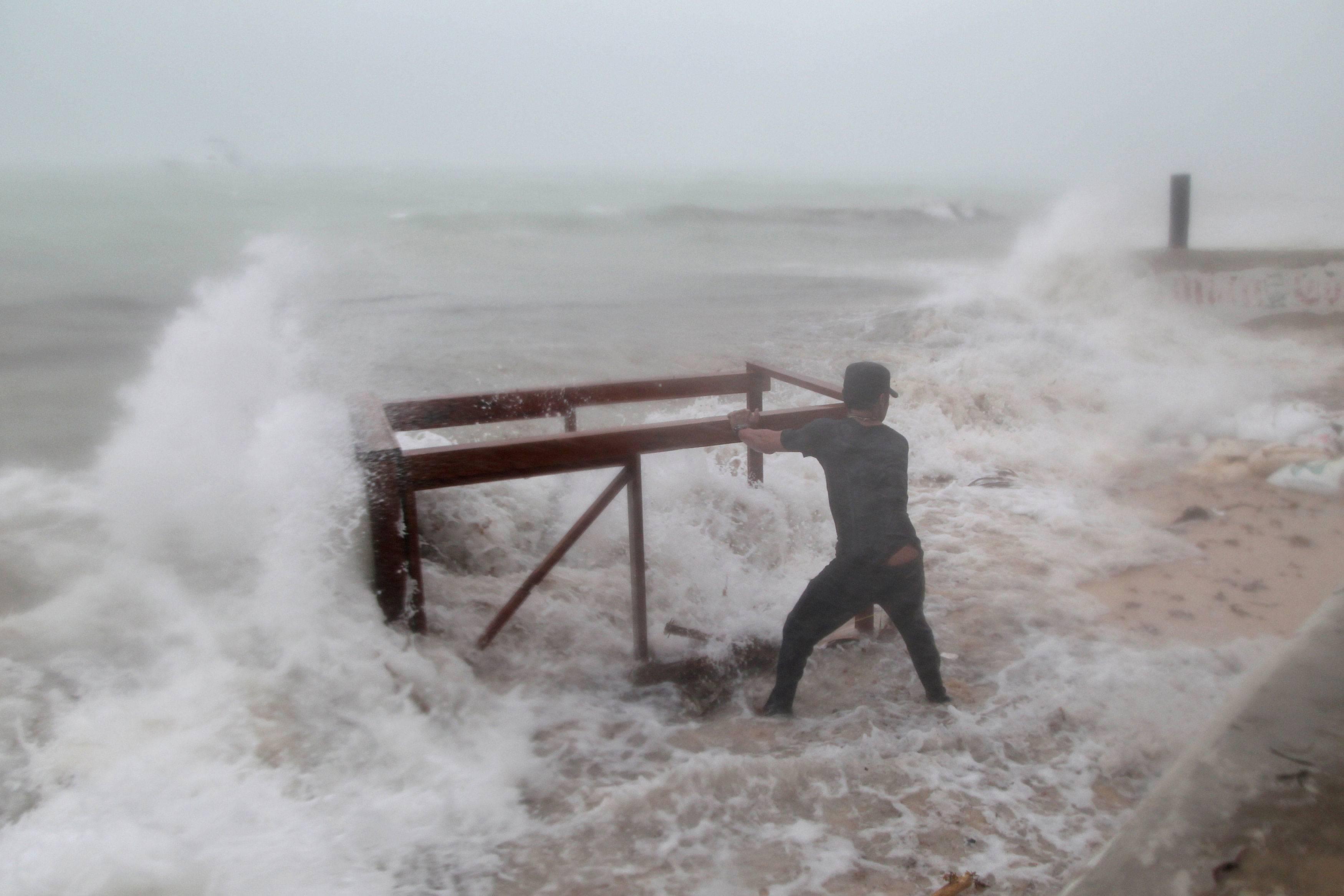 Homem tenta impedir que água leve mesa de restaurante antes da chegada de do furacão em Punta Cana, na República Dominicana