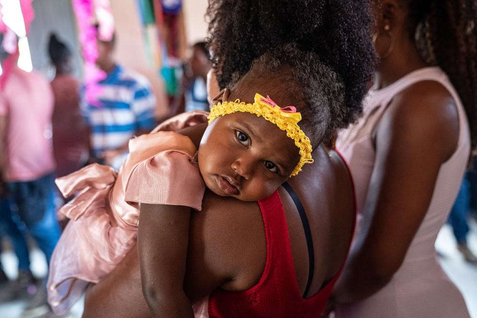 Criança sendo batizada na capela do Vão de Almas, no Quilombo Kalunga. Padre da cidade vai apenas uma vez por ano - durante os festejos - realizar batizados e casamentos na comunidade — Foto: Fábio Tito/G1